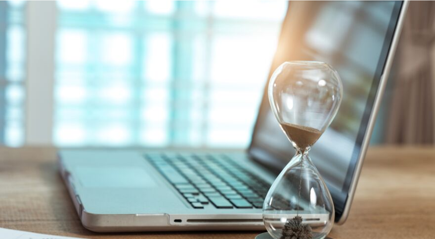 Laptop with Hourglass indicates that automation in inventory management software saves time
