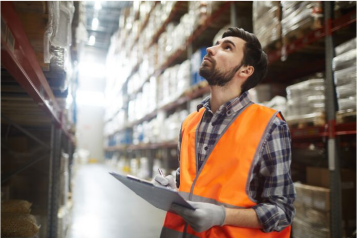 A man standing in the warehouse with notepad in his hands. He is counting products.